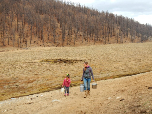 Helping our guide's young daughter fetch water for dinner. Northern Mongolia.