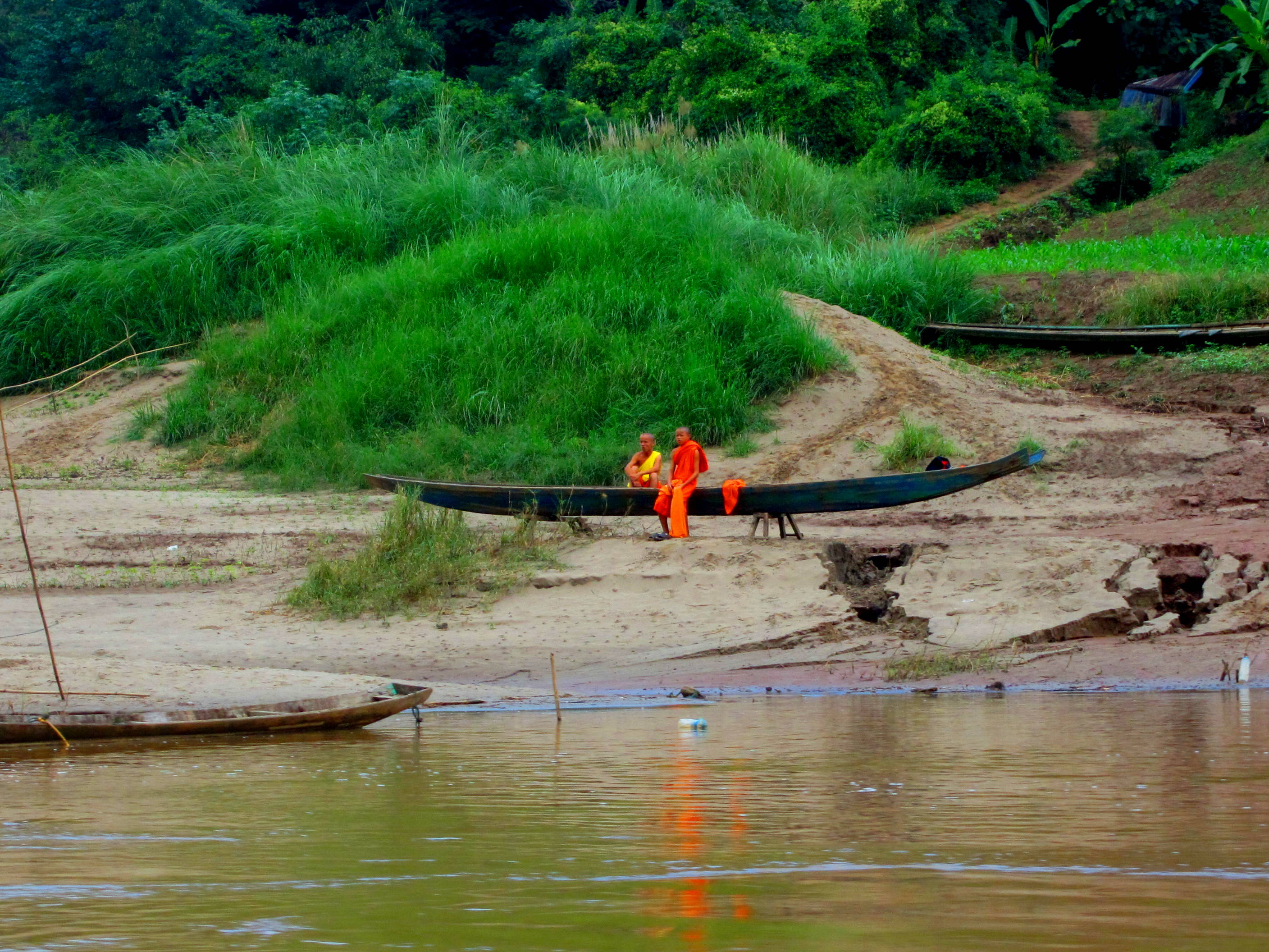 Monks on the riverbank. Taking the riverboat from Laos back to Thailand