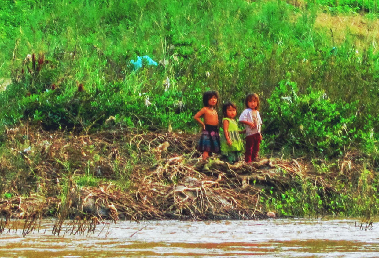 Children on the bank. Taking the riverboat from Laos back to Thailand