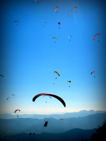 The sky in Pokhara is filled with paragliders-- Flying at the top of the world. Nepal.