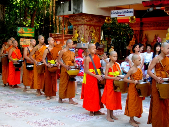 Monks collecting offerings at the Buddhist monastery in Khon Kaen, Thailand